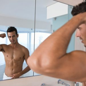 Man flexing bicep in bathroom mirror