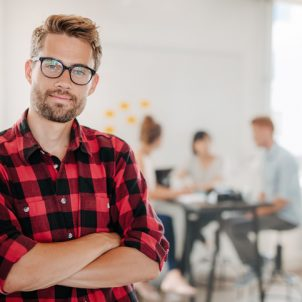 Portrait of a positive looking young business professional standing with his arms crossed with coworkers talking in the background.