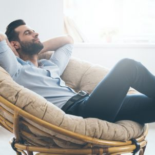 Handsome young man keeping eyes closed and holding hands behind head while sitting in big comfortable chair at home