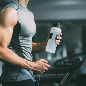 Unrecognisable young man in sportswear running on treadmill at gym and holding bottle of water