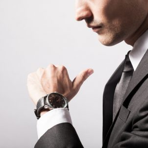 Businessman checking the time on his wrist watch.